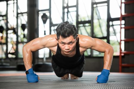 Hombre musculoso atractiva que hace pectorales en piso del gimnasio Foto de archivo