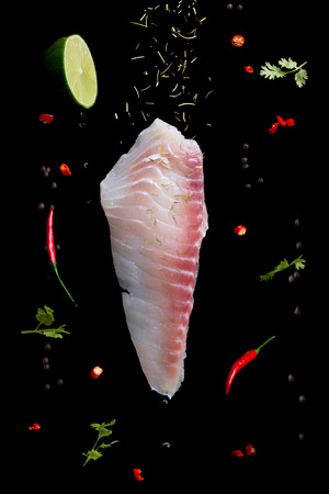 crushed red peppers: raw Fish fillet with herbs and spices in motion on black background 02 Stock Photo