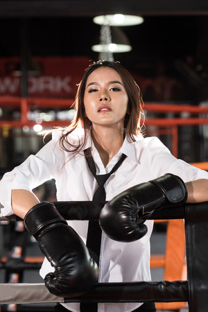 woman with boxing gloves: Young Asian businesswoman with boxing glove on boxing ring. Winner and business success concept Stock Photo