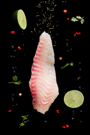 Raw Fish fillet with herbs and spices in motion on black background.