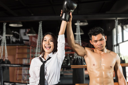 winning business woman: Winning business woman celebrating wearing boxing gloves and business suit on boxing ring. Winner and business success concept Stock Photo