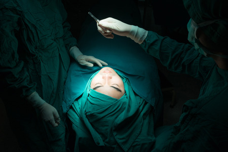 Plastic surgery wrinkle reduction , asian man during surgery using a scalpel , Plastic surgery. From above