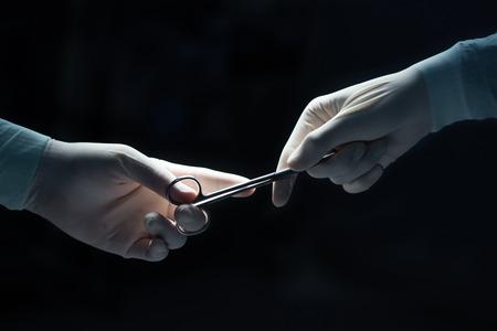 tijeras: cuidado de la salud y el concepto m�dico, primer plano de cirujanos manos sosteniendo tijeras quir�rgicas y pasando equipo quir�rgico en negro Foto de archivo