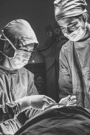 Two surgeons man works with a scalpel in operating room