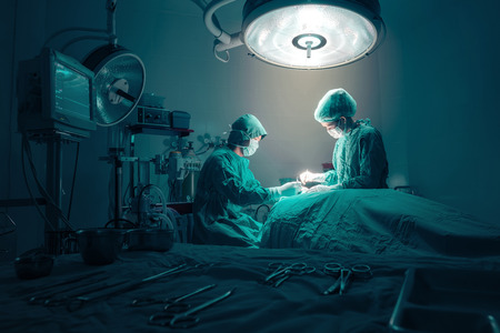 equipos medicos: Cirujanos equipo que trabaja con la supervisi�n del paciente en la sala de operaciones quir�rgicas. Foto de archivo