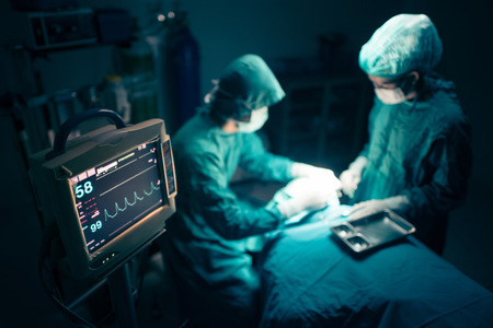 cirujano: Cirujanos equipo que trabaja con la supervisi�n del paciente en la sala de operaciones quir�rgicas. enfoque selectivo en el monitor.