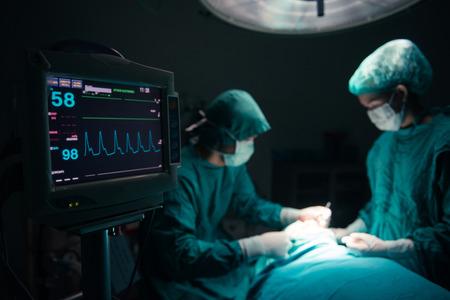 paciente: Personas de los cirujanos que trabajan con monitoreo de pacientes en sala de operaciones quirúrgicas. atención selectiva en el monitor Foto de archivo