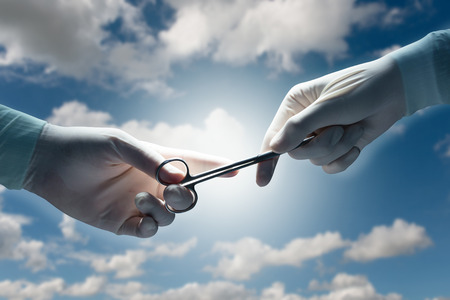 by pass surgery: healthcare and medical concept , Close-up of surgeons hands holding surgical scissors and passing surgical equipment on a cloudy sky background. Stock Photo