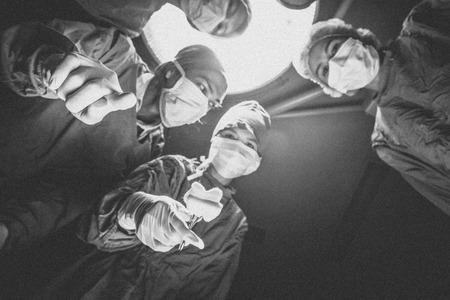 specific clothing: Surgeons team standing above of the patient before surgery. selective focus on hand Stock Photo