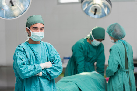 arms crossed: Surgeon with arms crossed looking at camera with colleagues performing in background
