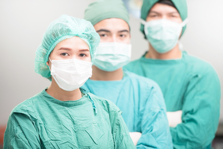 surgeons: Surgeons team, man and woman wearing protective uniforms,caps and masks.