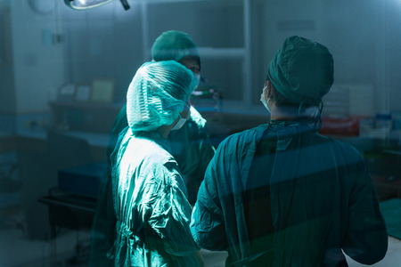 Surgery team speaking to each other at operating room Banque d'images