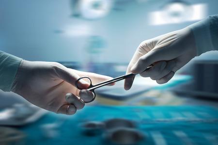 la asistencia sanitaria y médica concepto, Primer plano de cirujanos manos sosteniendo tijeras quirúrgicas y pasando equipo quirúrgico, fondo de desenfoque de movimiento.