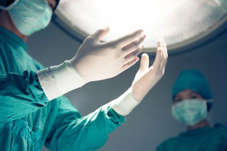toga y birrete: las manos en guantes quirúrgicos en la sala de operación en el fondo de la lámpara quirúrgica Foto de archivo