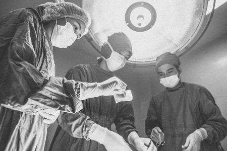 specific clothing: Surgeons team standing above of the patient before surgery with equipment , selective focus on hand Stock Photo