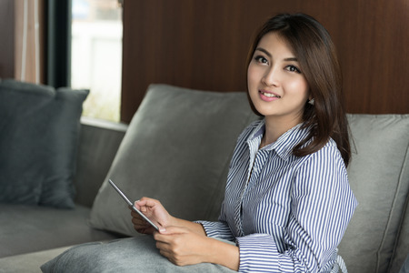 usando computadora: happy young asian woman using digital tablet pc on sofa in the living room at home Foto de archivo