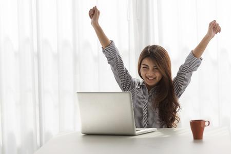 興奮した女性が彼女の家で彼女のラップトップに取り組んでいる間彼女の腕を上げる