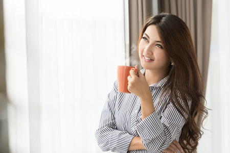 tomando café: Mujer asiática que bebe el café en casa