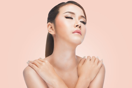 beautiful background: Young asian woman with crossed arms. clean skin resting after skincare, on pink background. beautiful Spa Perfect Fresh Skin, Youth and Skin Care Concept. Stock Photo