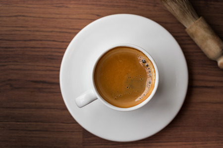 espresso: cup of fresh espresso with cleaning blush of coffee machine on table, view from above