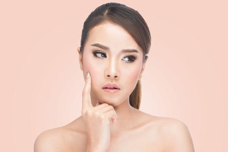 mujer pensando: retrato de la hermosa mujer de pensamiento asiático natural y expresiva y mirando hacia abajo, en el fondo de color rosa con saturación camino. Foto de archivo