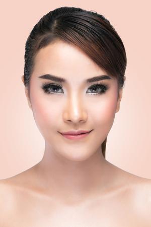 portada: Chica de belleza. Retrato de mujer joven hermosa que mira la cámara. Perfecta piel fresca que presenta en el estudio sobre fondo de color rosa con el camino de recortes. La piel limpia fresca