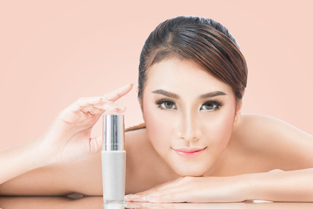 skincare products, Portrait of Beautiful Young Woman looking at Camera. Beautiful Asian female model on pink background