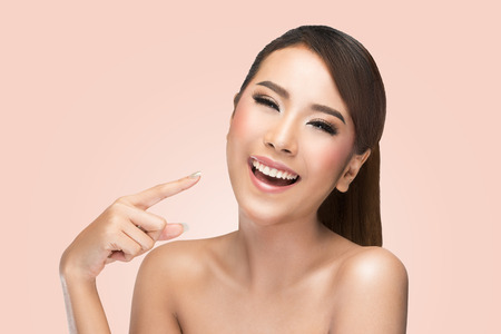 美しさ: 肌ケア美容女性彼女の顔を指していると幸せで陽気な笑みを浮かべて笑っています。ピンクの背景にアジア女性の美モデル。