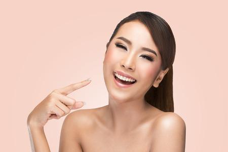 아름다움: 스킨 케어 뷰티 우먼 그녀의 얼굴을 가리키고 행복하고 명랑 웃는 웃음. 분홍색 배경에 아시아 여성의 아름다움 모델입니다.