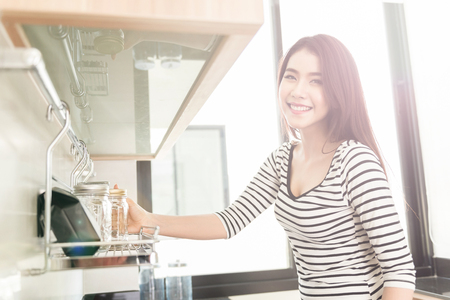 太陽光線とレンズのフレア、ノイズ、フィルムの穀物のモダンなキッチンでガラスを保持している美しい若い女性はトーン イメージです。 写真素材