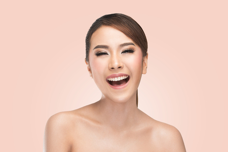 Beauty portrait of skin care beauty woman laughing smiling happy and cheerful. Asian female beauty model on pink background. Standard-Bild