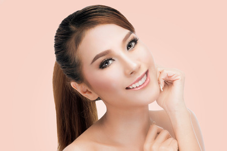 asia nude: Spa Woman Portrait. Beautiful Asian Girl Touching her Face. Perfect Fresh Skin. Pure Beauty Model Female looking at camera. Youth and Skin Care Concept.on pink background with clipping path. Stock Photo