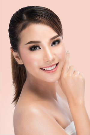Spa Woman Portrait. Beautiful Asian Girl Touching her Face. Perfect Fresh Skin. Pure Beauty Model Female looking at camera. Youth and Skin Care Concept.on pink background with clipping path. Banque d'images