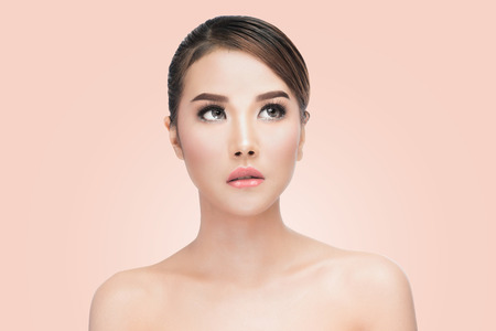 soft skin: Beauty Asian Woman face Portrait. Beautiful Spa model Girl with Perfect Fresh Clean Skin. looking up. Youth and Skin Care Concept. on pink background with clipping path Stock Photo