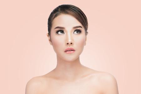 piel humana: Belleza asiática Cara de la mujer del retrato. Modelo hermoso de la muchacha del balneario con Perfect Clean Fresh Skin. buscando. Juventud y Cuidado de la piel Concept. en el fondo de color rosa con trazado de recorte