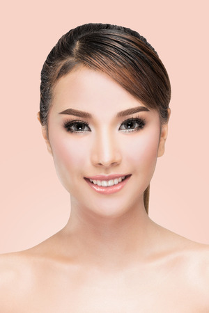 Beauty Asian Woman face Portrait. Beautiful Spa model Girl with Perfect Fresh Clean Skin. looking at camera. Youth and Skin Care Concept. on pink background with clipping path