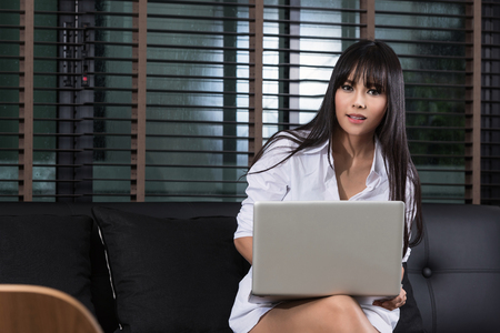 asian businesswoman: Business woman at home using laptop, sitting in living room, looking at camera. Stock Photo