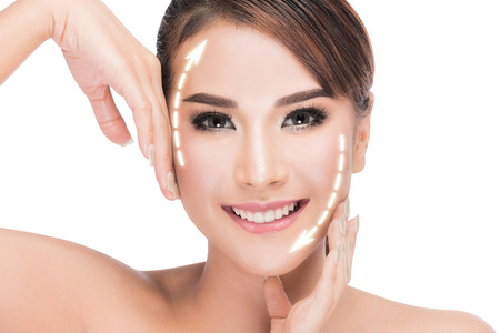 aging: beauty, plastic surgery, aging, people and health concept - beautiful young woman touching her face with lifting arrows isolated on white with clipping path