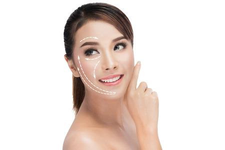 la beauté, la chirurgie plastique, le vieillissement, les gens et le concept de santé - belle jeune femme de toucher son visage avec des flèches isolé sur blanc avec chemin de détourage de levage Banque d'images