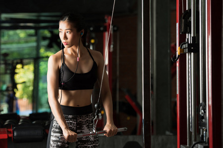 asian abs: Fitness woman, Asian woman flexing arm muscles on cable machine in gym