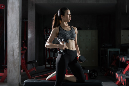 Asian fitness girl with perfect shape body workout lifting a dumbbell in the gym,Fitness woman Stockfoto