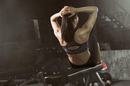 Asian woman doing sit-ups at gym, Abdominal exercises Sit up.