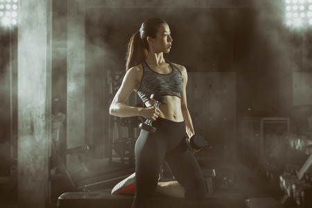 Toned picture,Asian fitness girl with perfect shape body workout lifting a dumbbell in the gym,Fitness woman