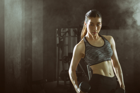 Toned picture,Asian fitness girl with perfect shape body workout lifting a dumbbell in the gym, Exercising with dumbbells. Stockfoto