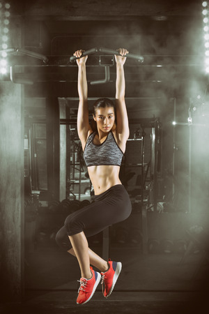 Toned picture,Fitness woman, Asian fitness girl with perfect shape body making eltions pull up in gym.