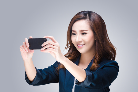 Young woman is taking photos with the mobile phone camera photo