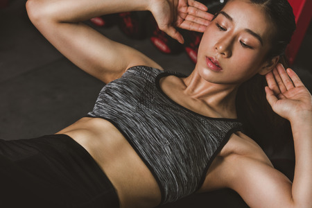 Athletic young woman exercise doing sit-up, push up at gym. Stockfoto