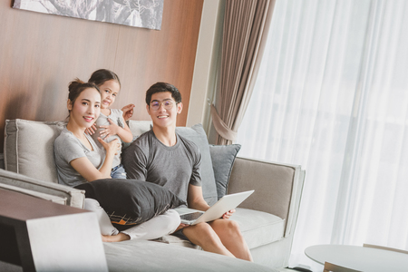 Happy parents with daughter using laptop in living room