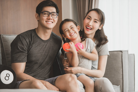 Happy parents with daughter in living room