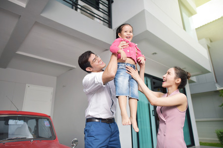 Happy parents with daughter in front of house Stockfoto